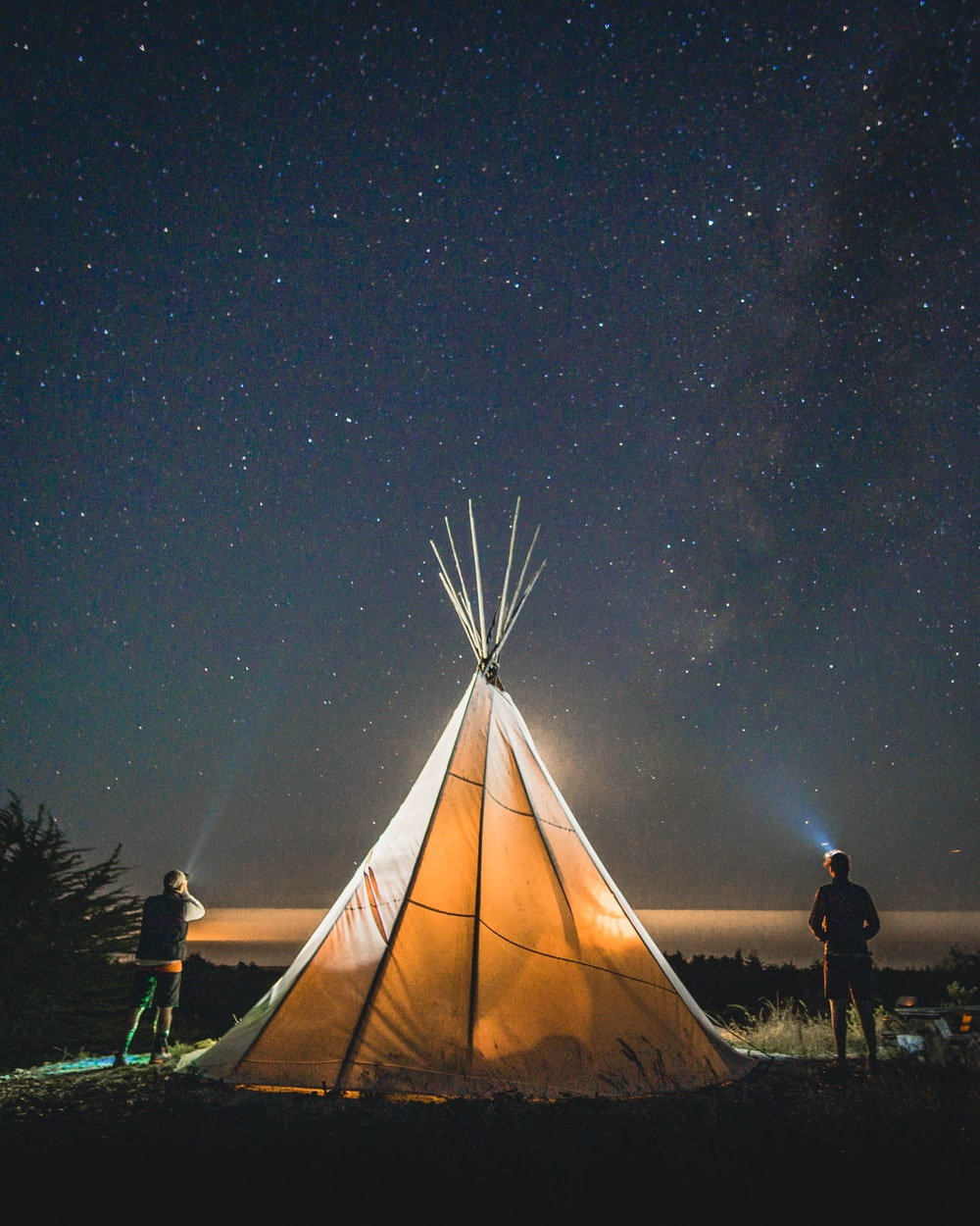 two person standing beside tent during nighttime