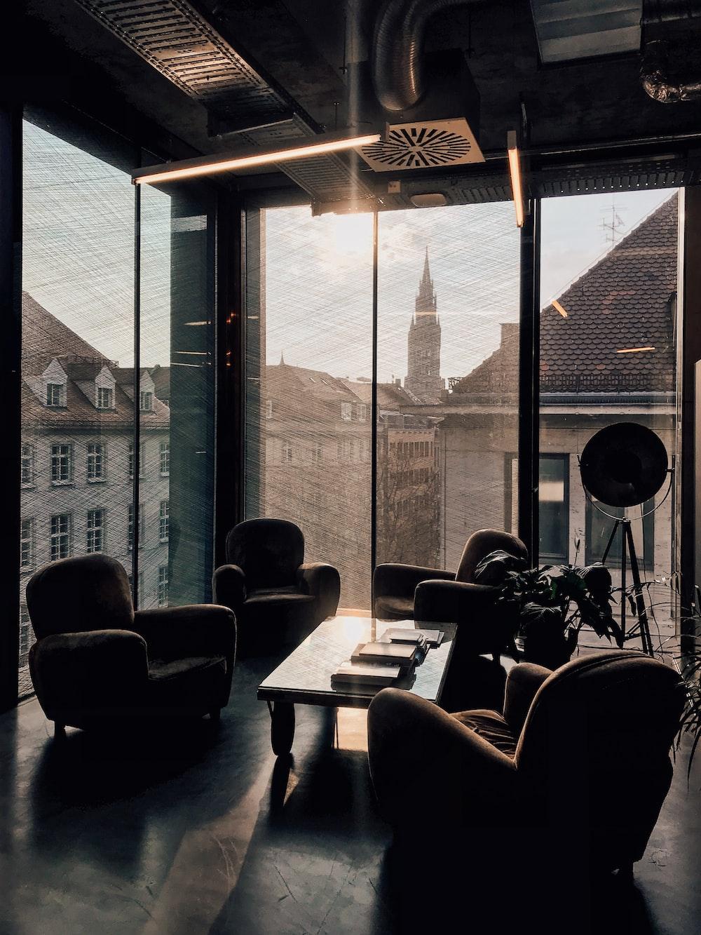 vacant sofa chairs beside glass window