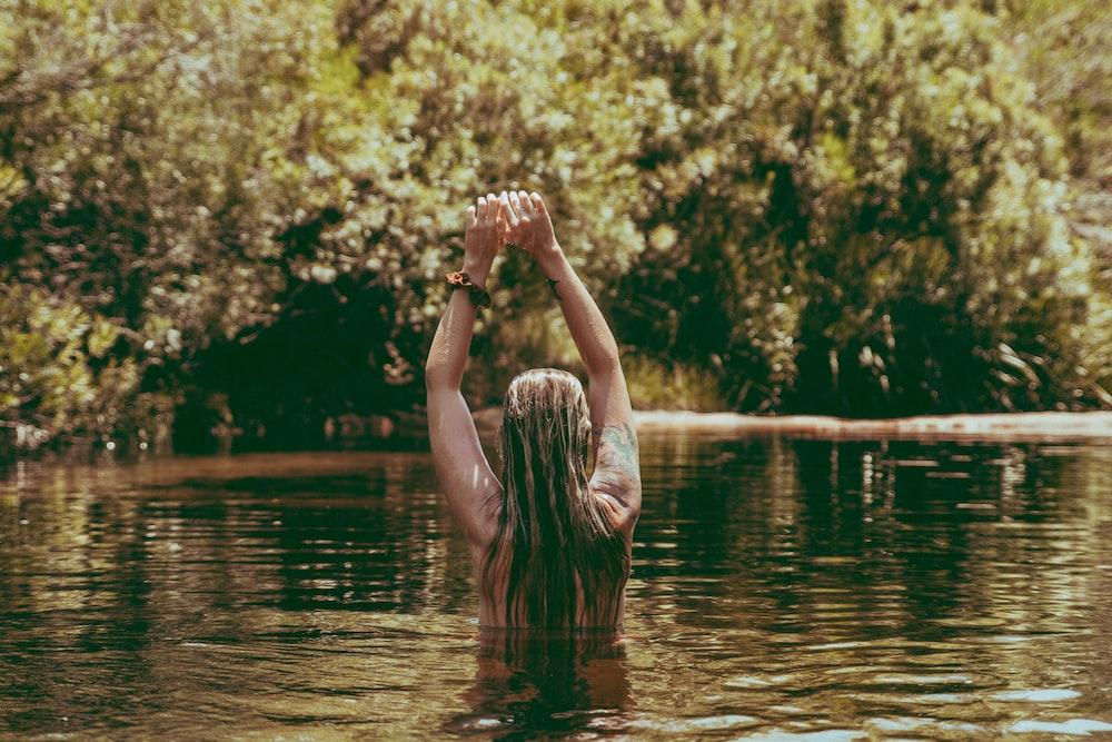person swimming on lake during daytime
