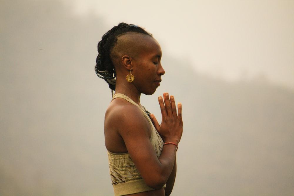 woman wearing brown crop top while praying