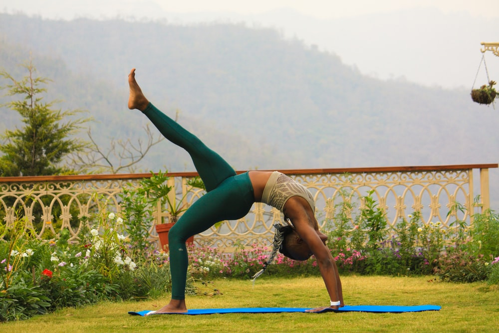 woman in teal leggings posing yoga