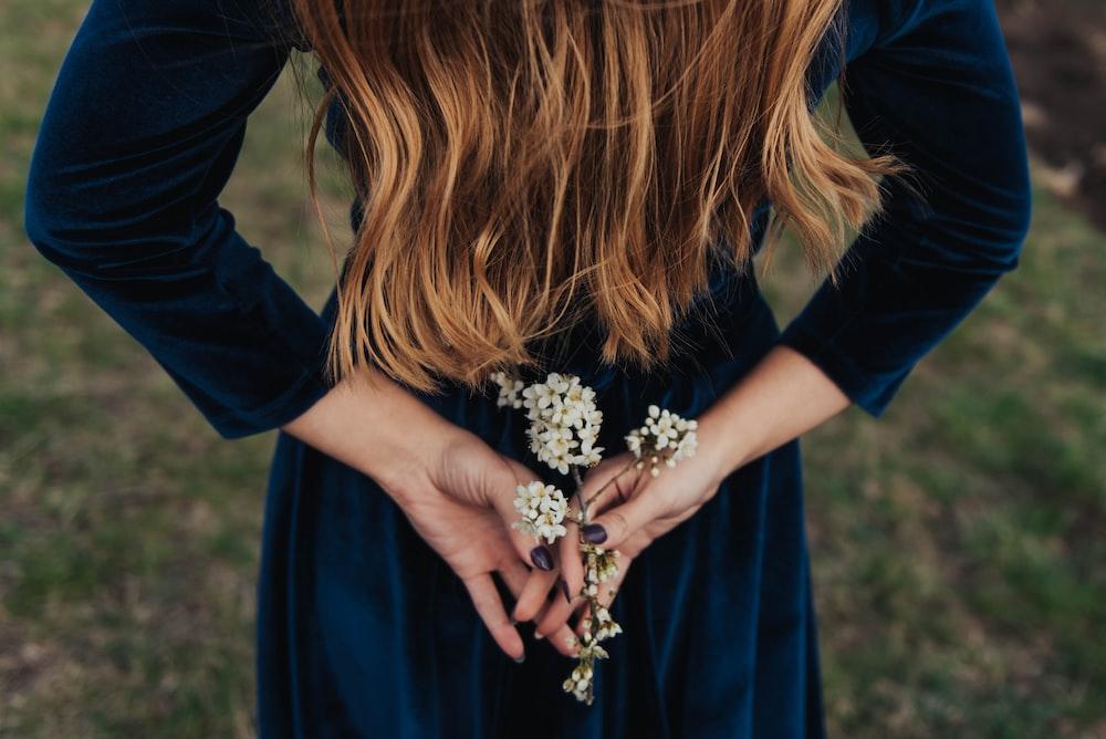 woman wearing blue long-sleeved shirt holding white flower