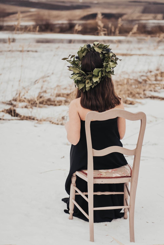 toddler wearing black tube dress sitting on brown wooden chair
