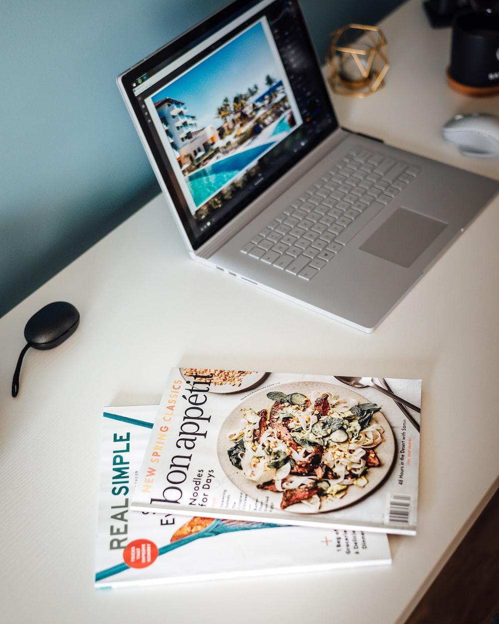 MacBook Pro beside magazines