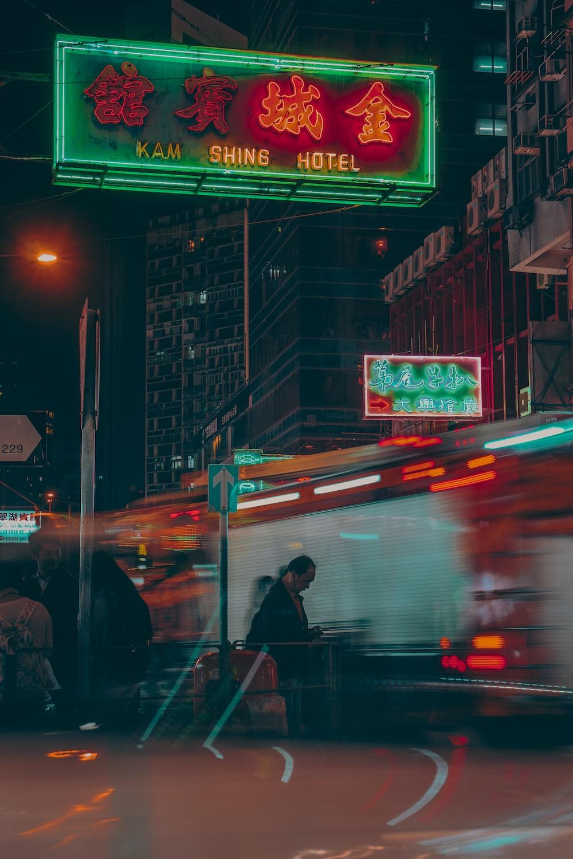 man wearing black jacket walking on street during nighttime