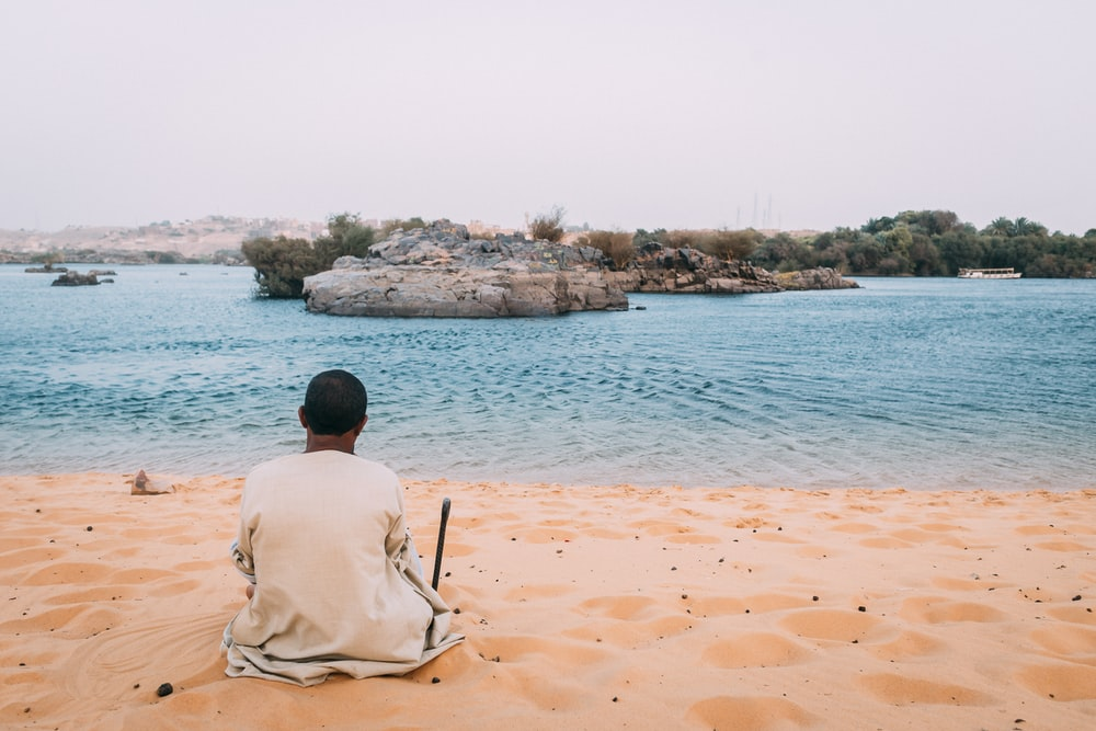 man sits on sand dunes while watching the beach