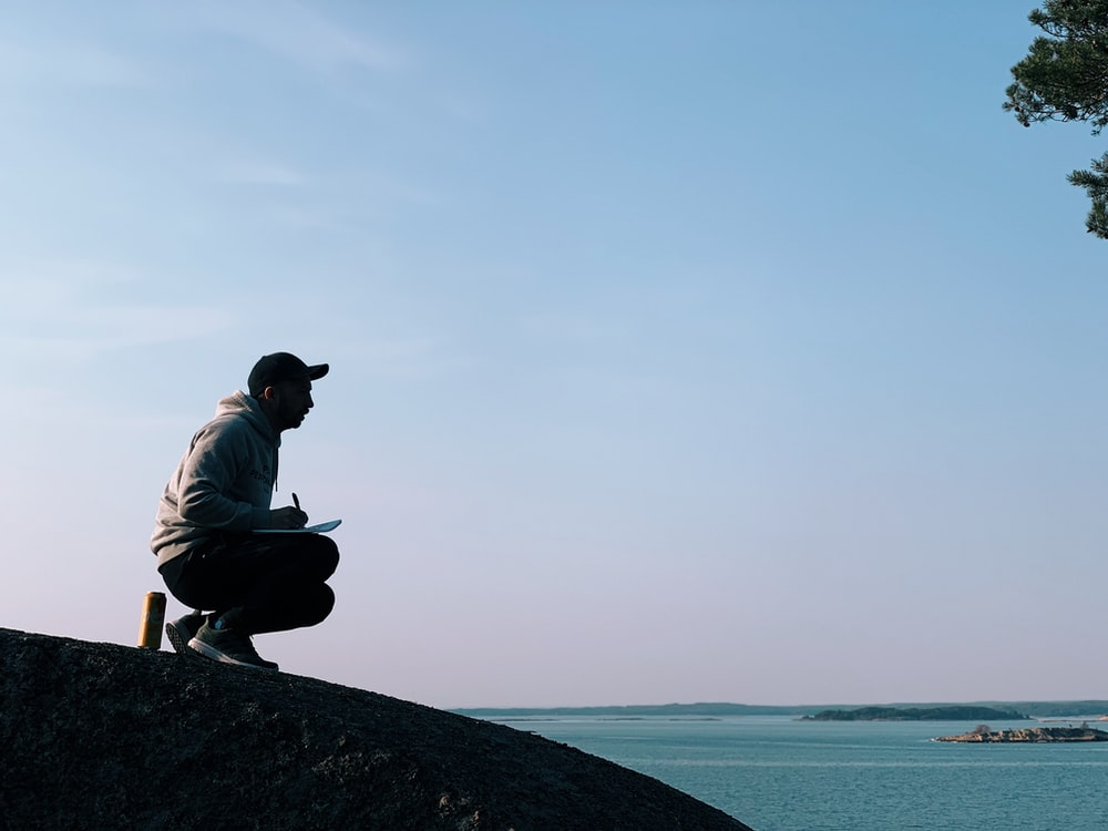 man sitting on hill during daytime near sea