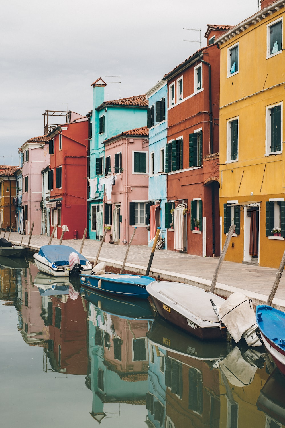 boats on calm body of water beside buildings