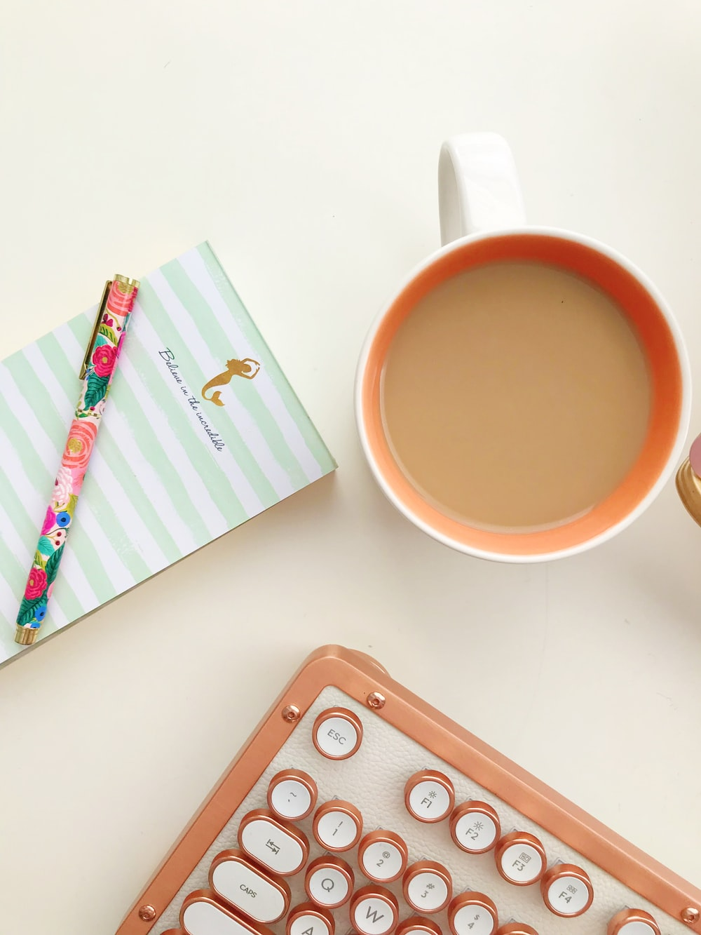 white and orange mug beside pen