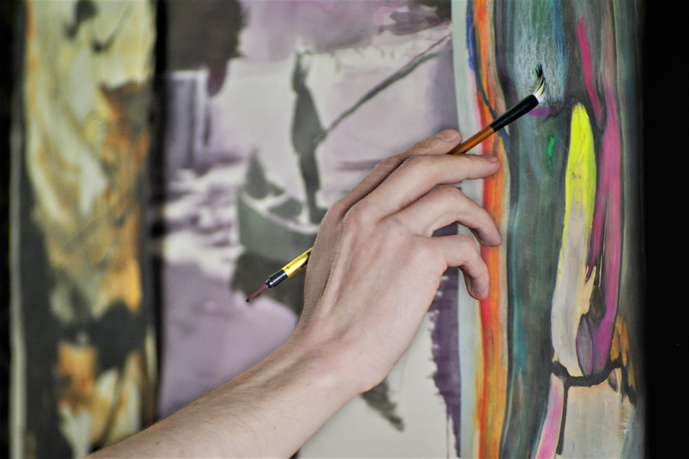 person holding paint brush while painting