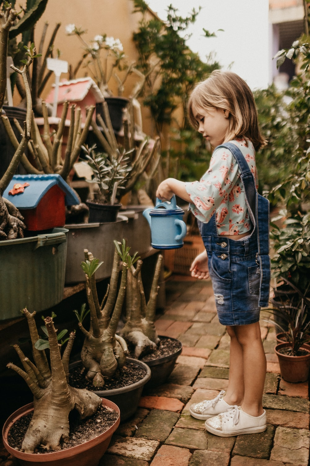 girl wearing blue romper holding teal watering can