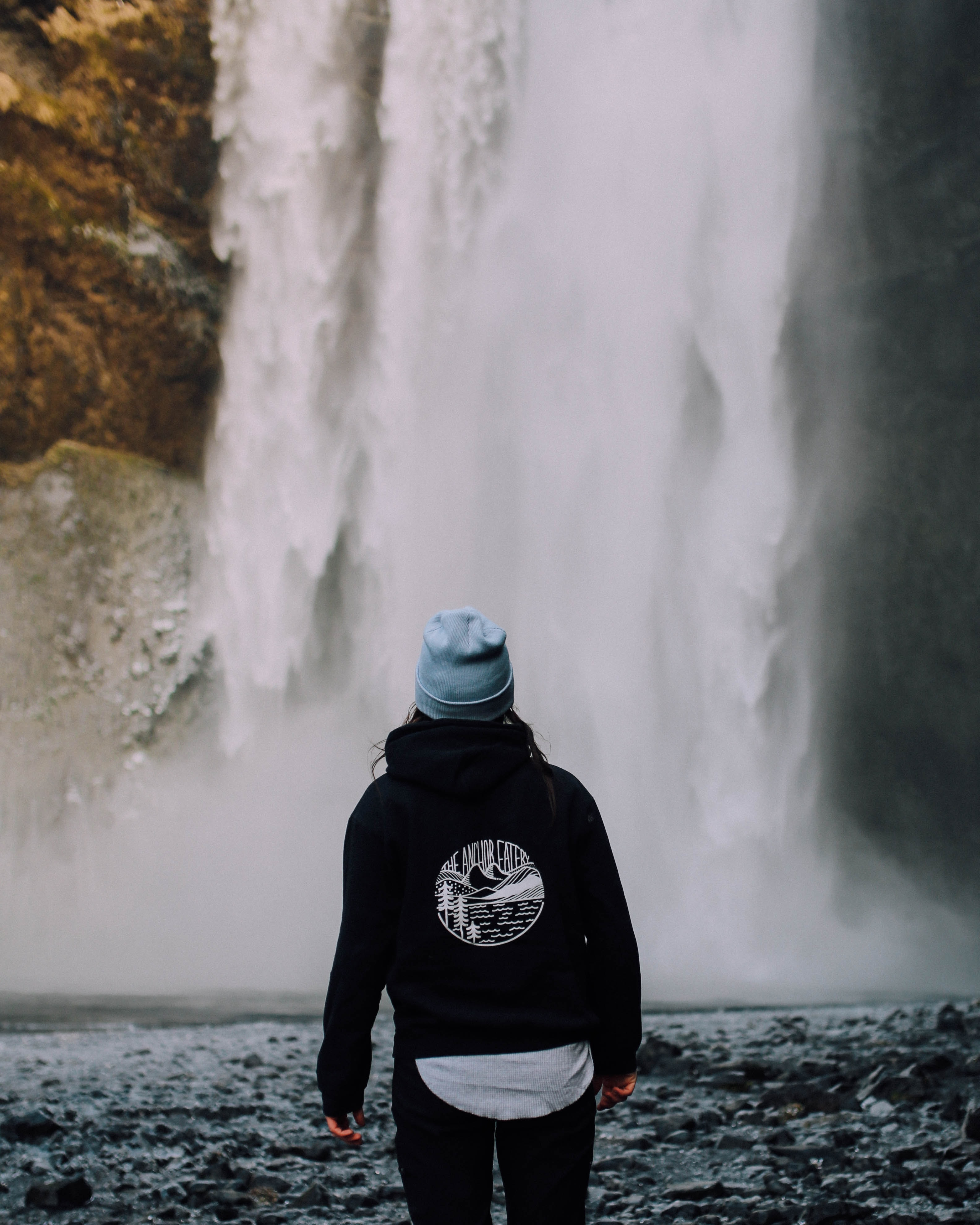 person standing near waterfalls during daytime