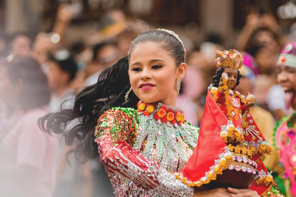 girl dancing while holding Sto.Nino figurine