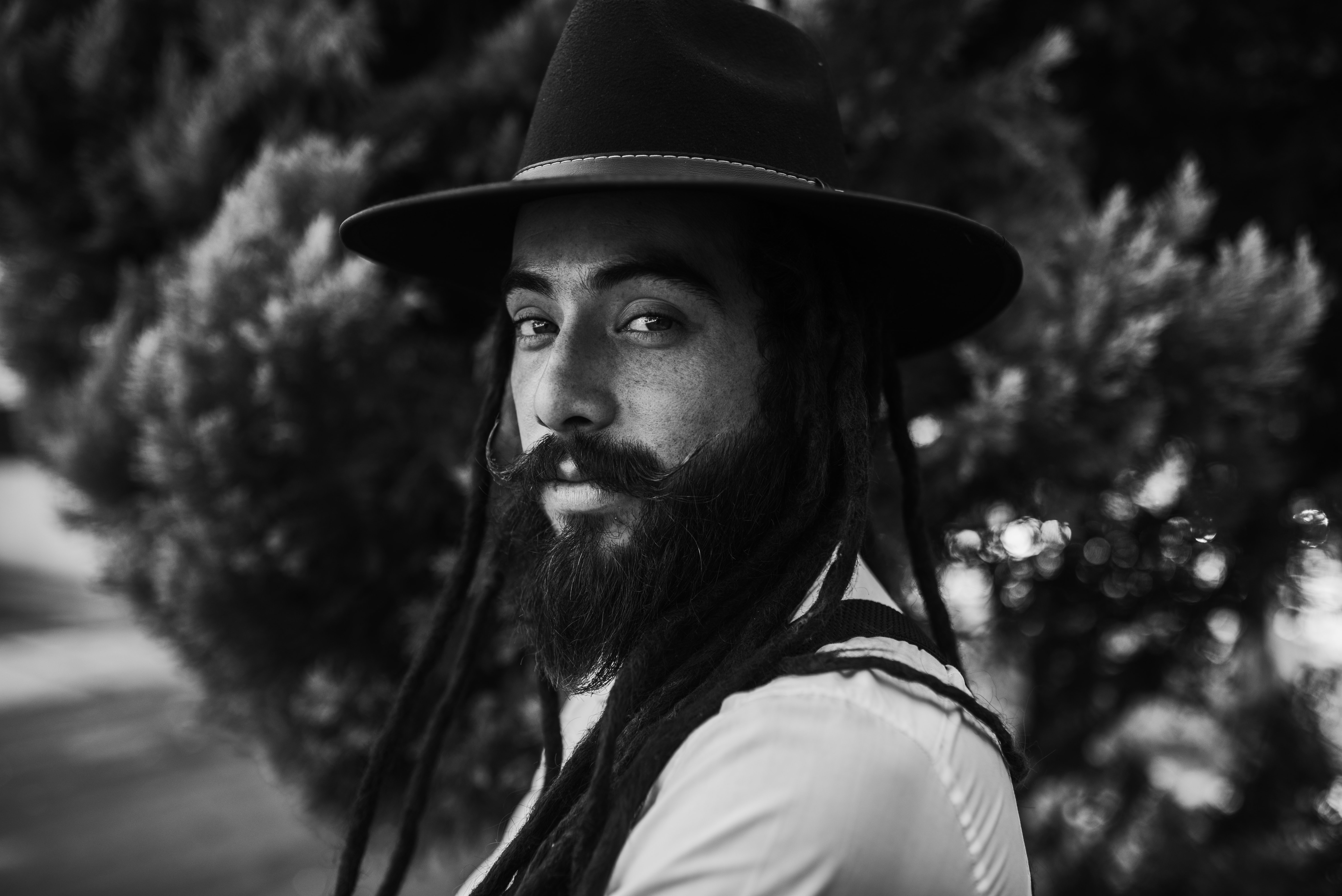 grayscale photo of man wearing black cap