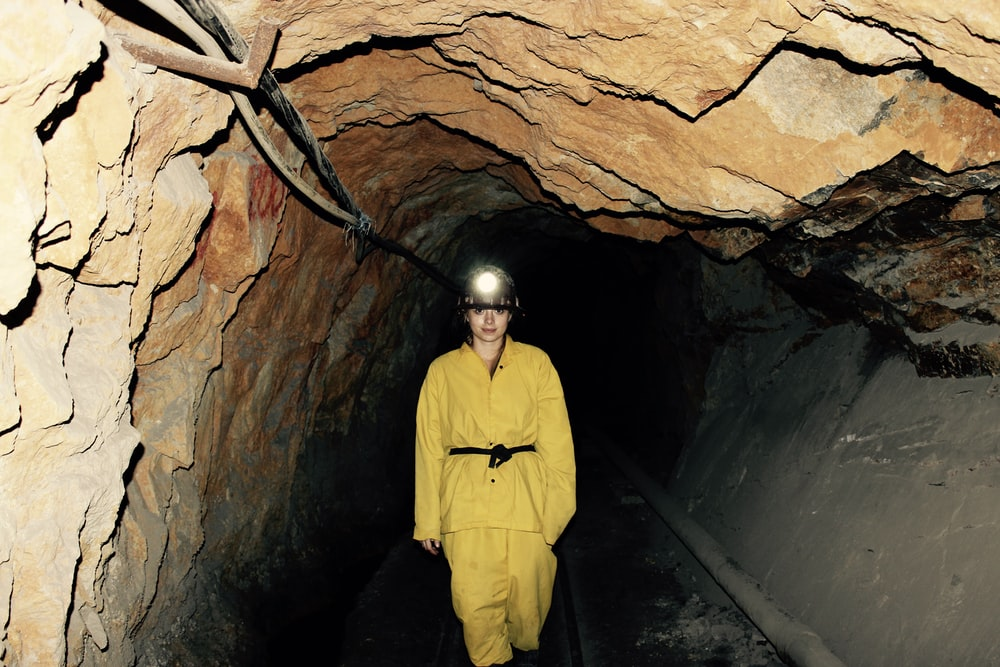 woman wearing yellow overall standing under cave