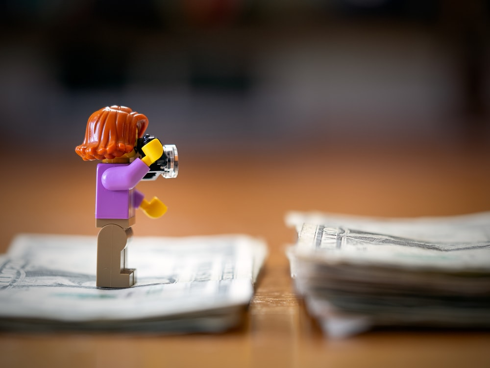 LEGO toy standing on dollar banknote