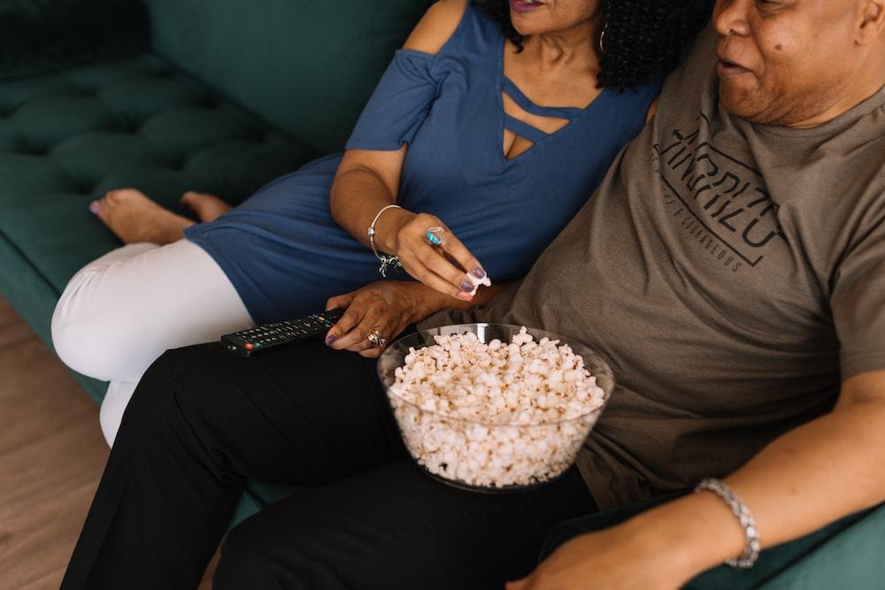 man sitting beside woman while picking popcorn