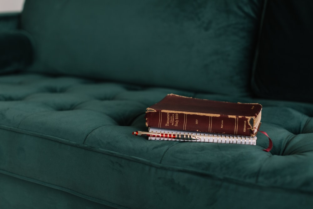 brown book on green tufted suede sofa