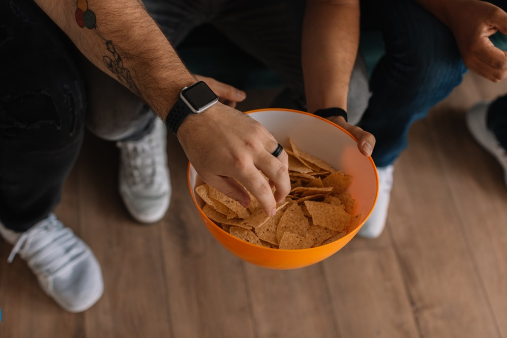 person holding orange bowl with potato chips