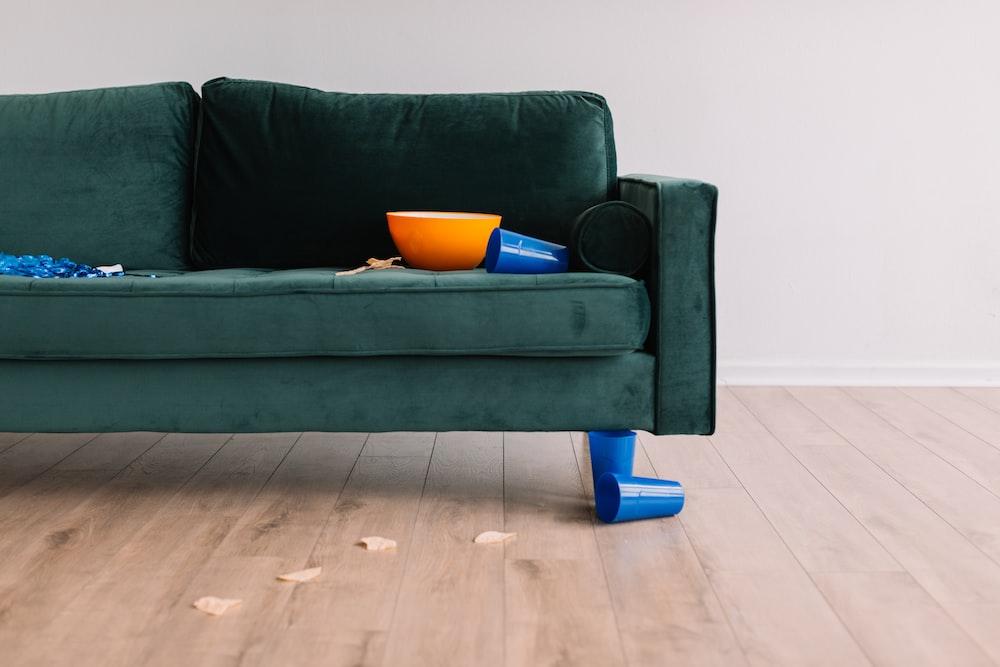 round orange plastic bowl on green sofa
