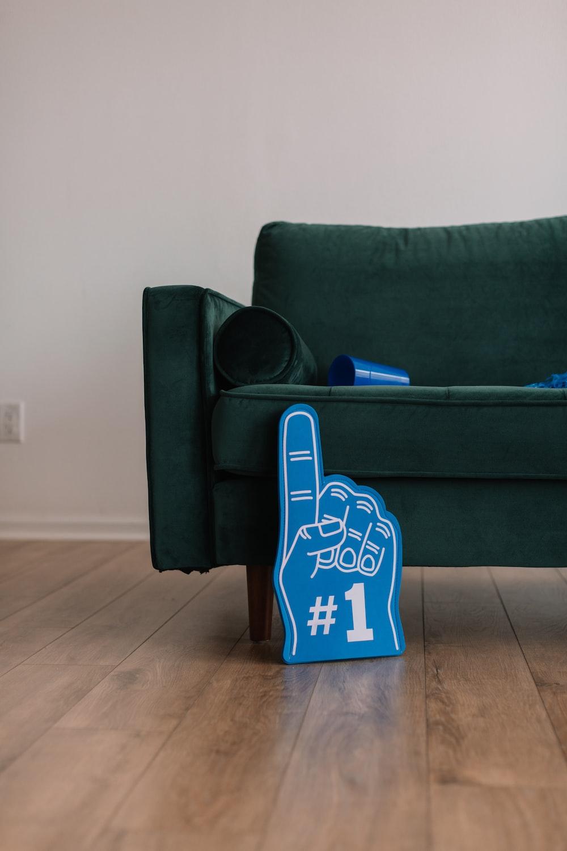 blue #1 finger sign beside green sofa