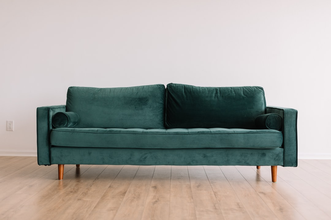 Cool hipster green couch sofa with brown wooden legs on wooden floor