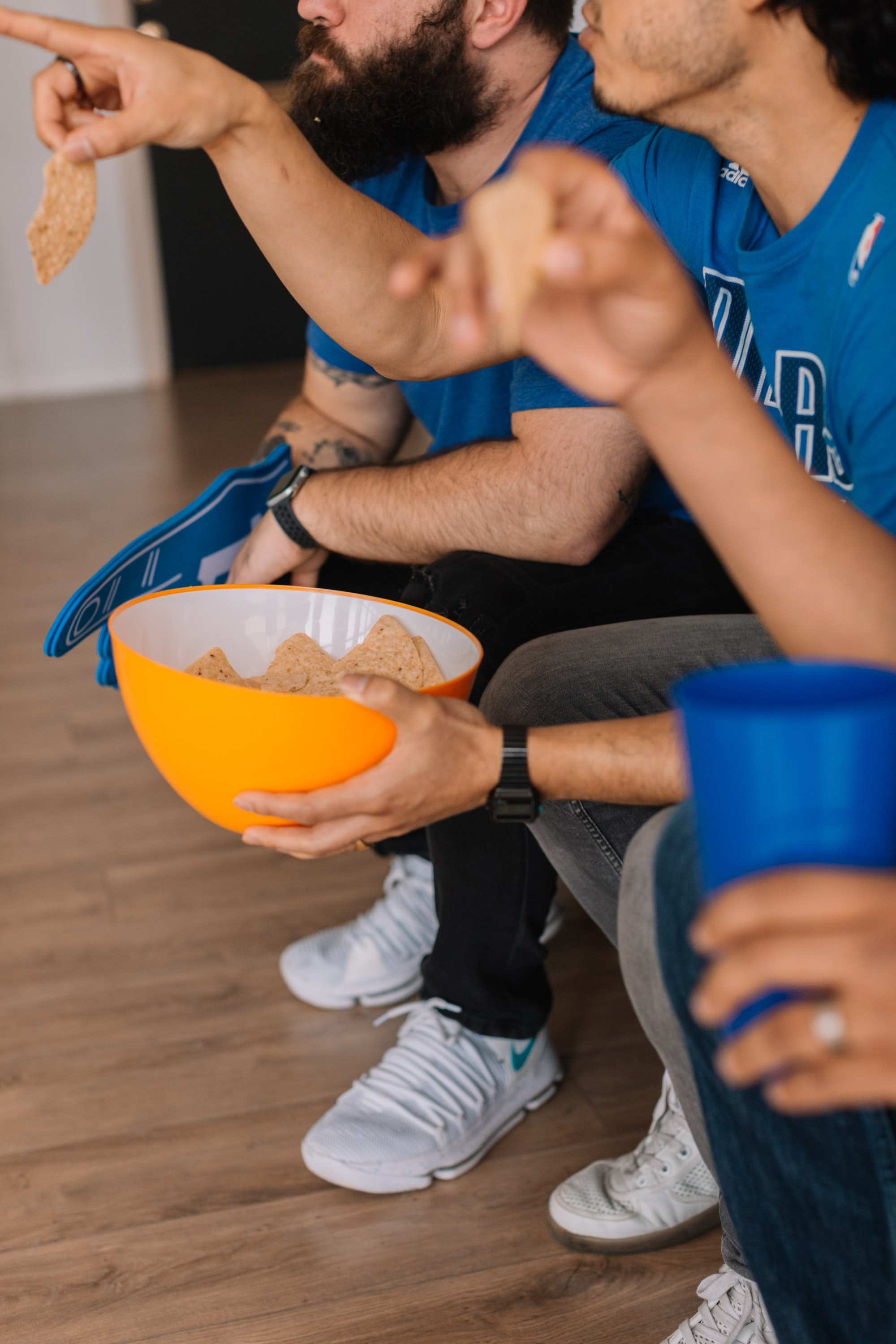 Group of friends watching a sports game on tv while eating chips and dressed in blue