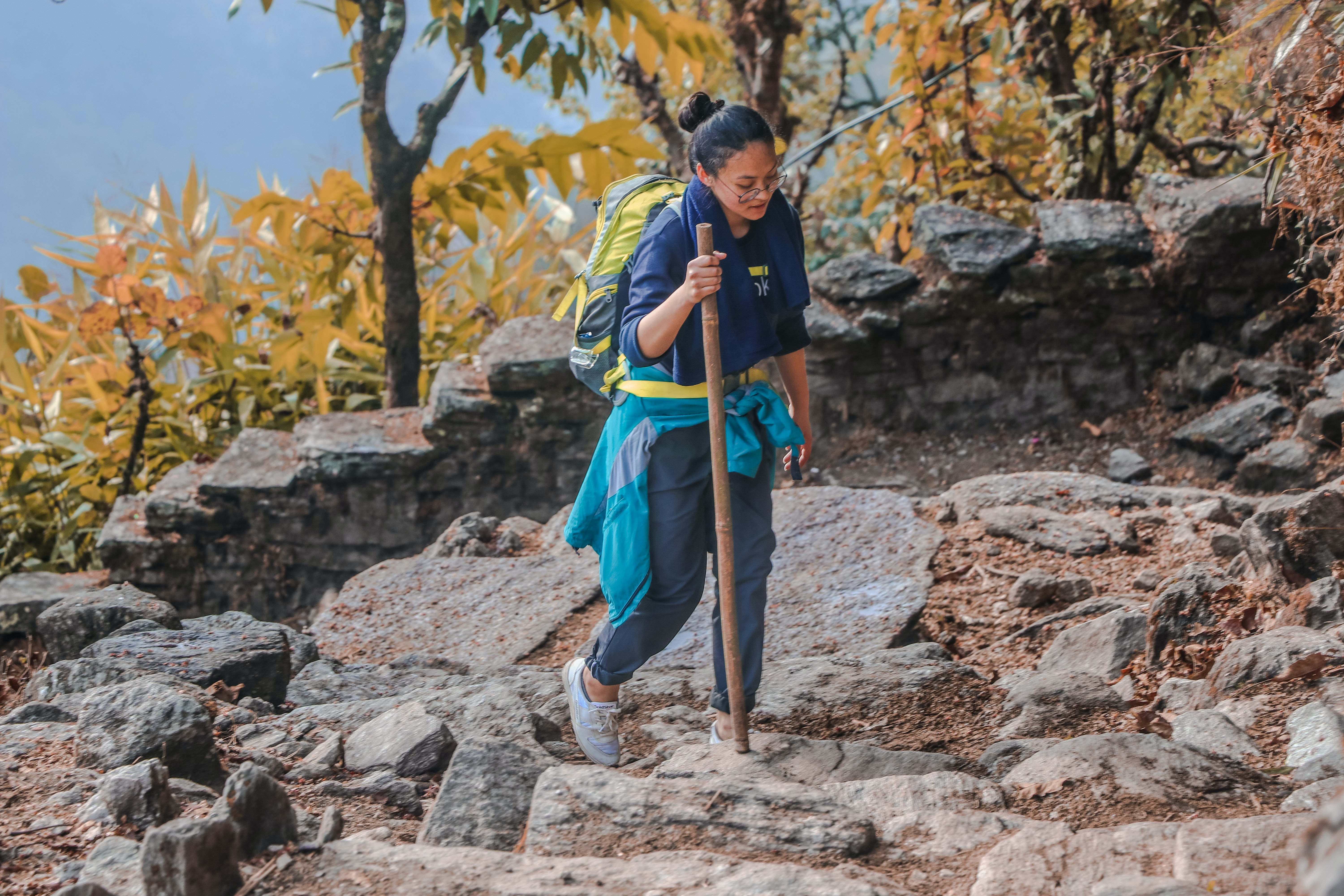 woman trekking on mountain carrying backpack and wooden stick
