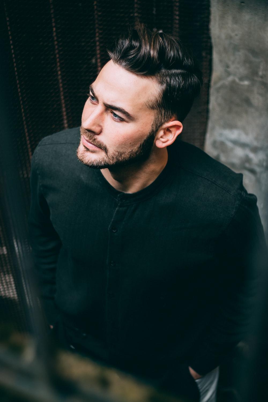 man wearing black crew-neck long-sleeved shirt