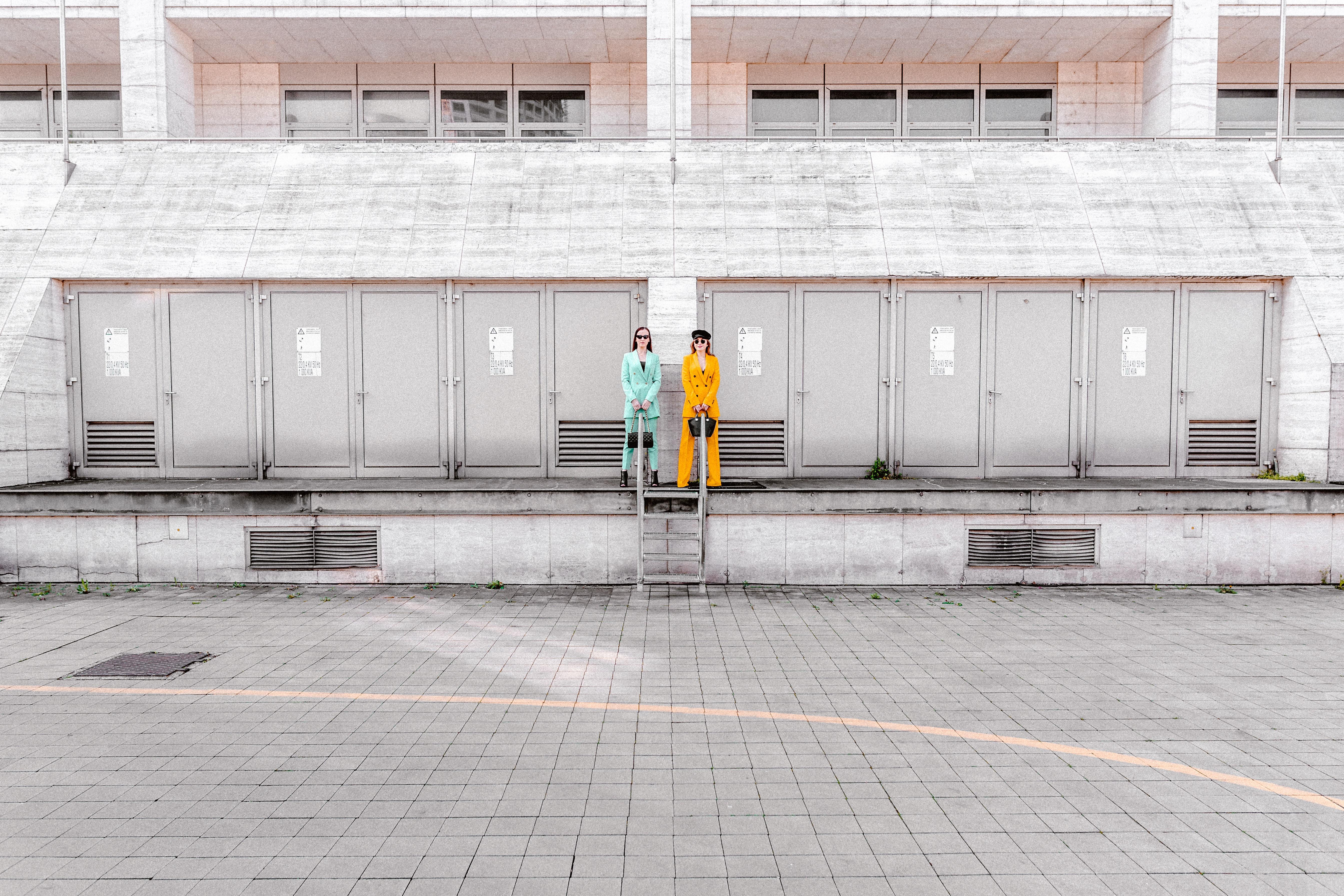 two women standing beside building