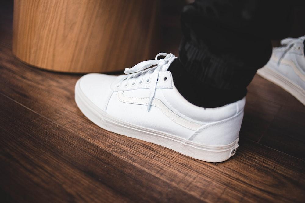 person wearing white Vans OldSkool low-top sneaker