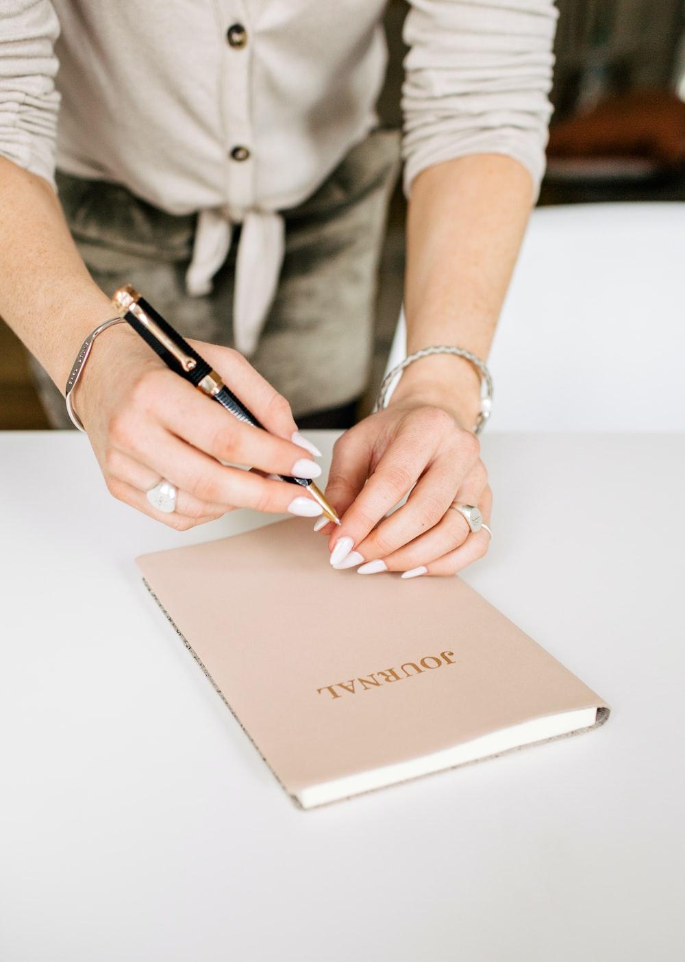 person holding pen near journal book