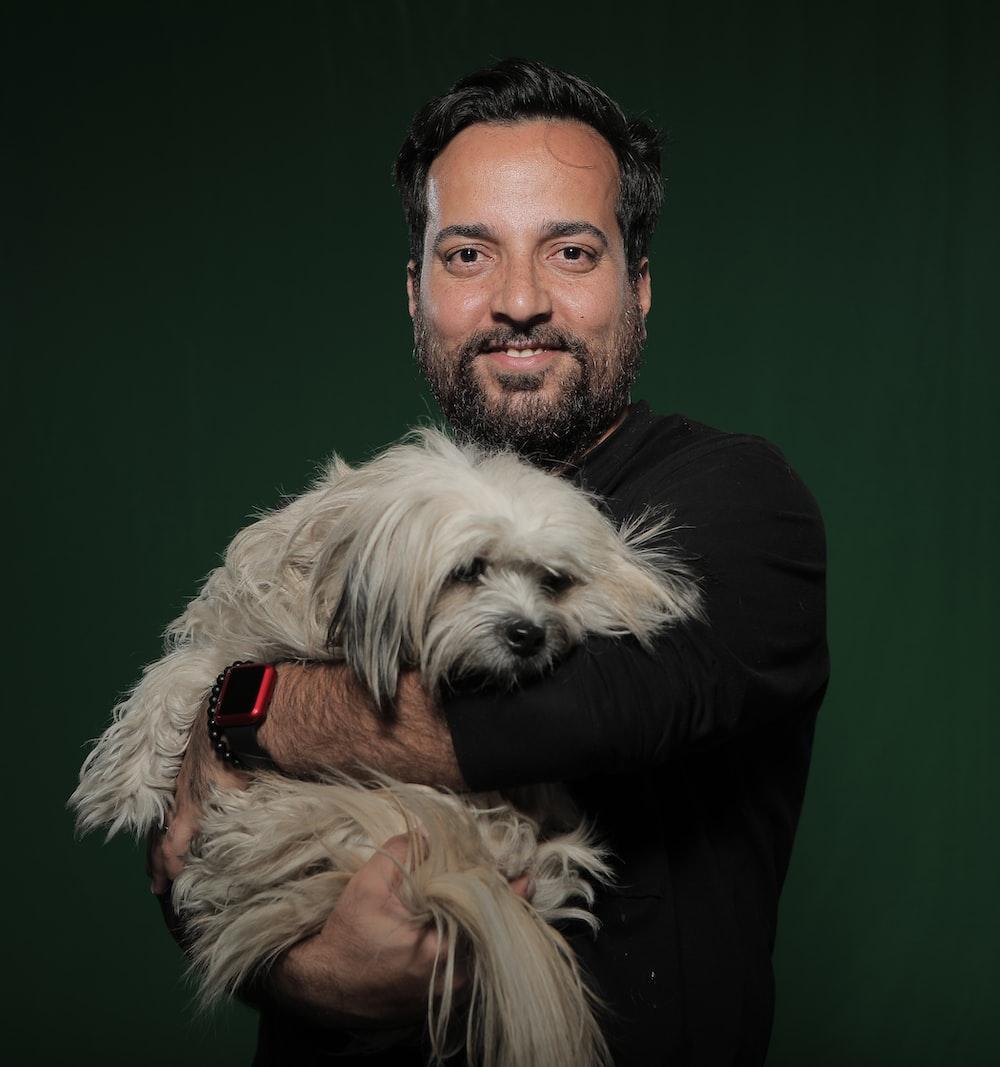 man holding white dog