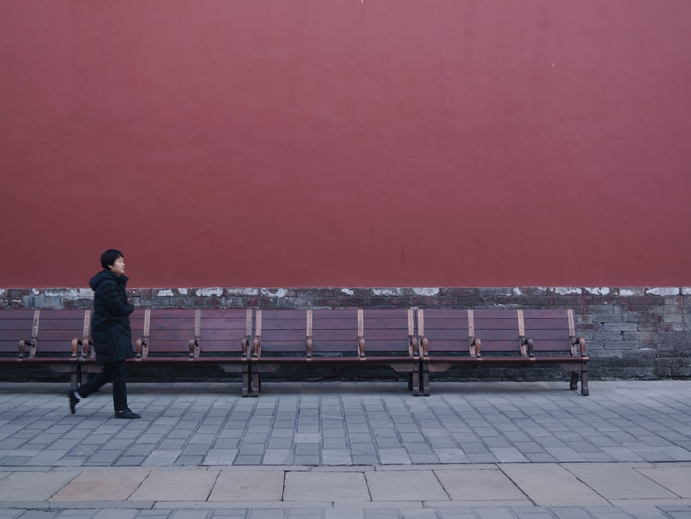 woman walking beside bench