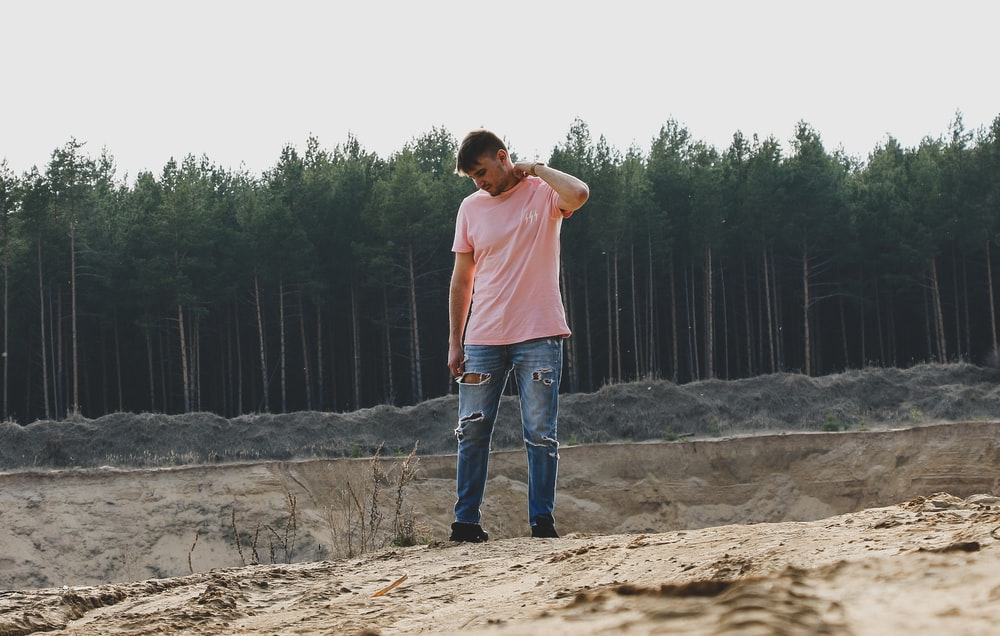man in pink t-shirt and blue jeans standing on ground