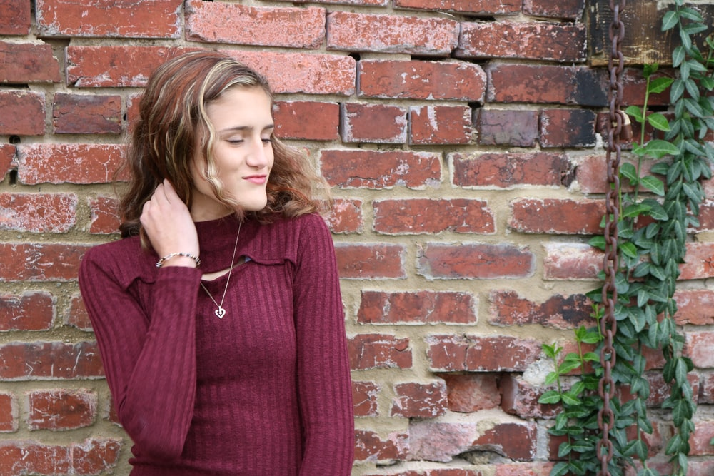 woman in purple sweater leaning against brick wall