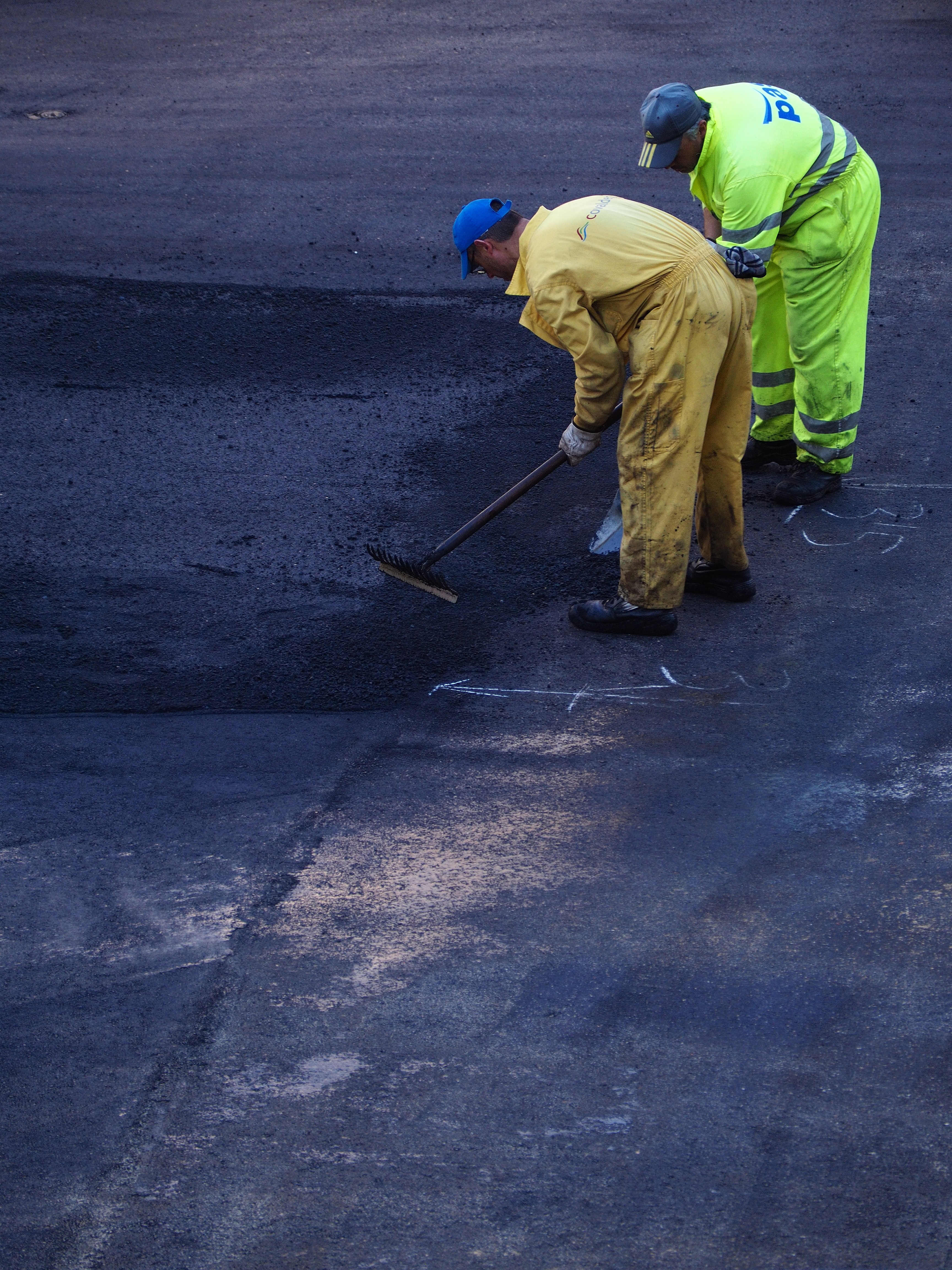 two man construct road during daytime