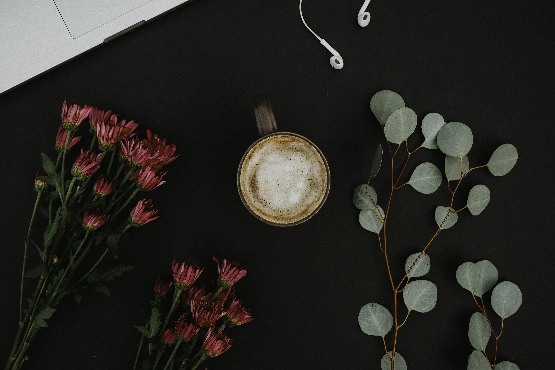 brown ceramic mug beside pink-petaled flowers on black surface