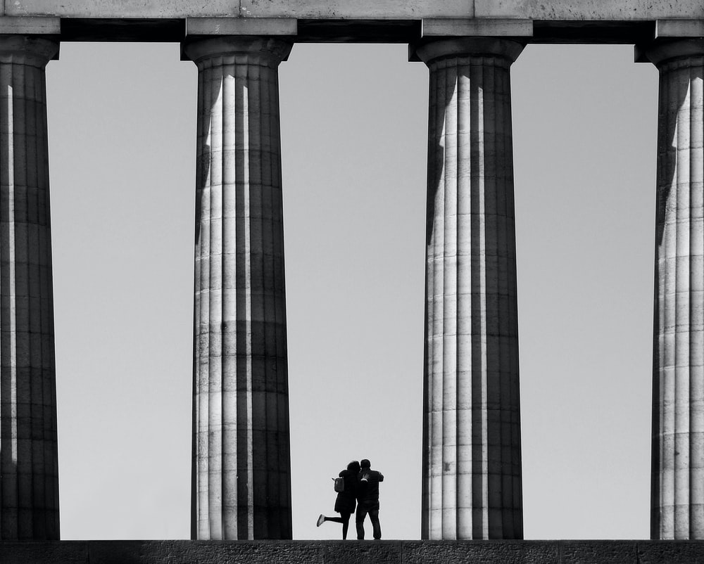 greyscale photo of silhouette of two person near columns