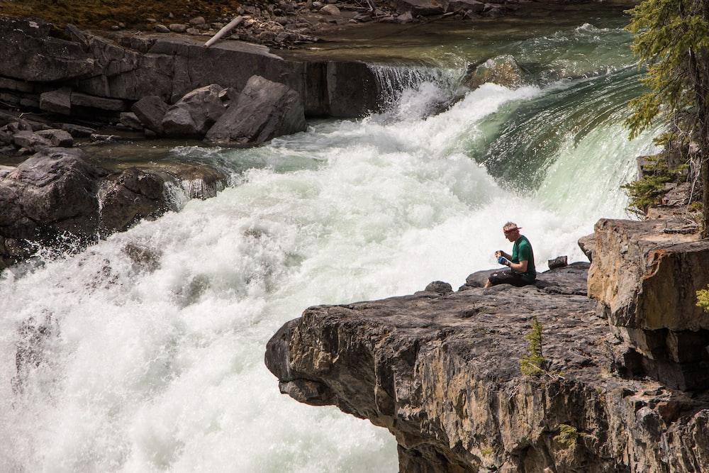 man sitting beside river during daytime