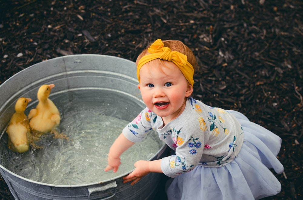 shallow focus photo of girl playing water
