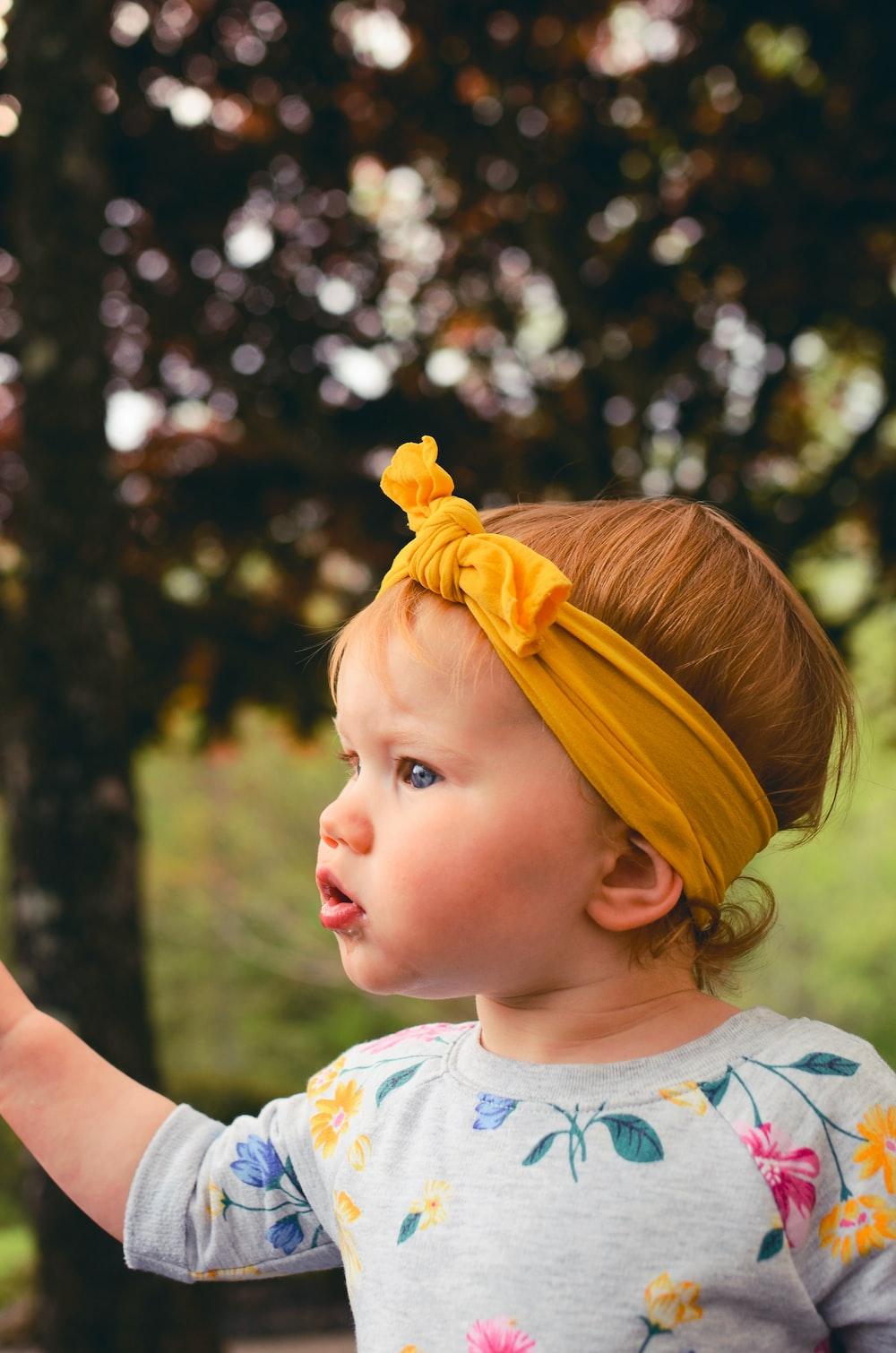 girl wearing gray shirt and yellow headband