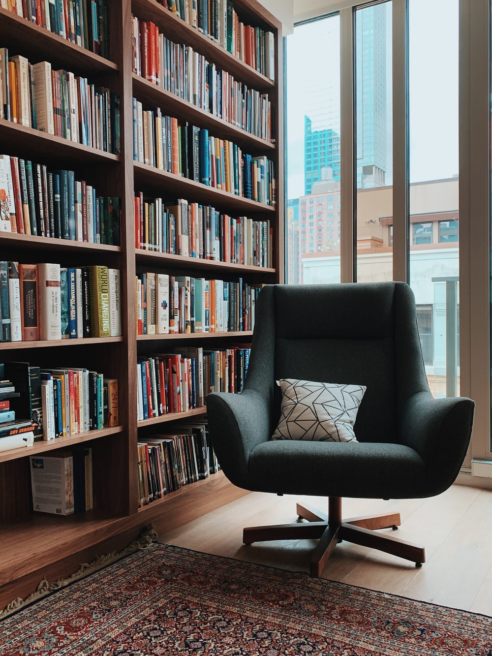 gray fabric padded rolling armchair near books