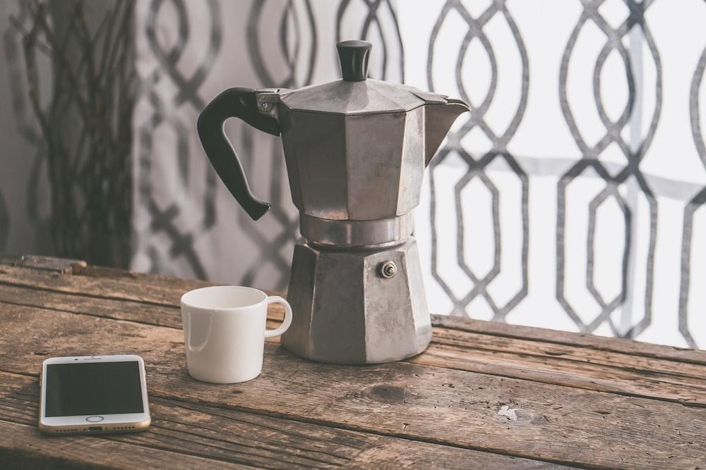 black handled gray kettle on brown wooden tabel