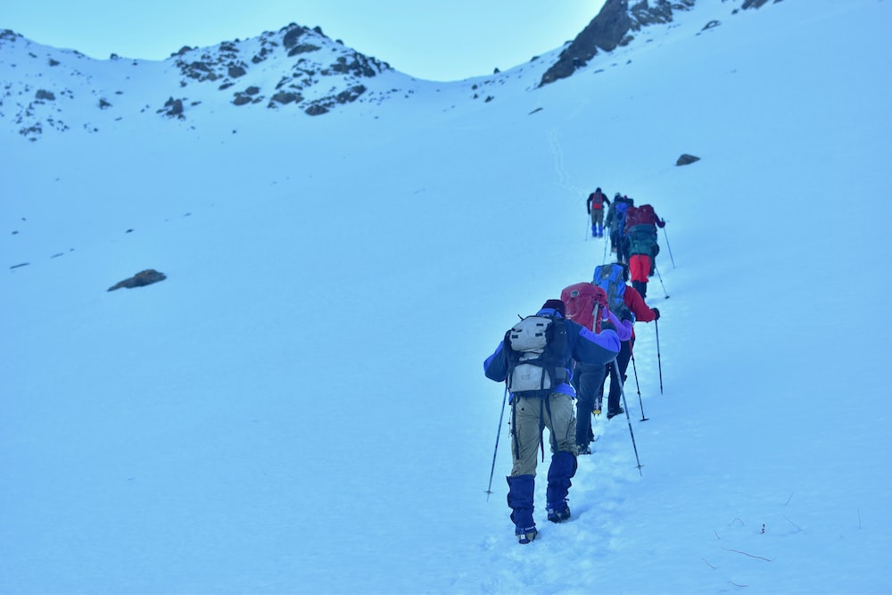 people climbing snow covered mountain during daytime