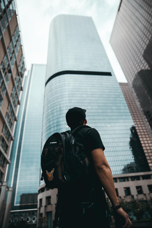 man standing near high rise buildings