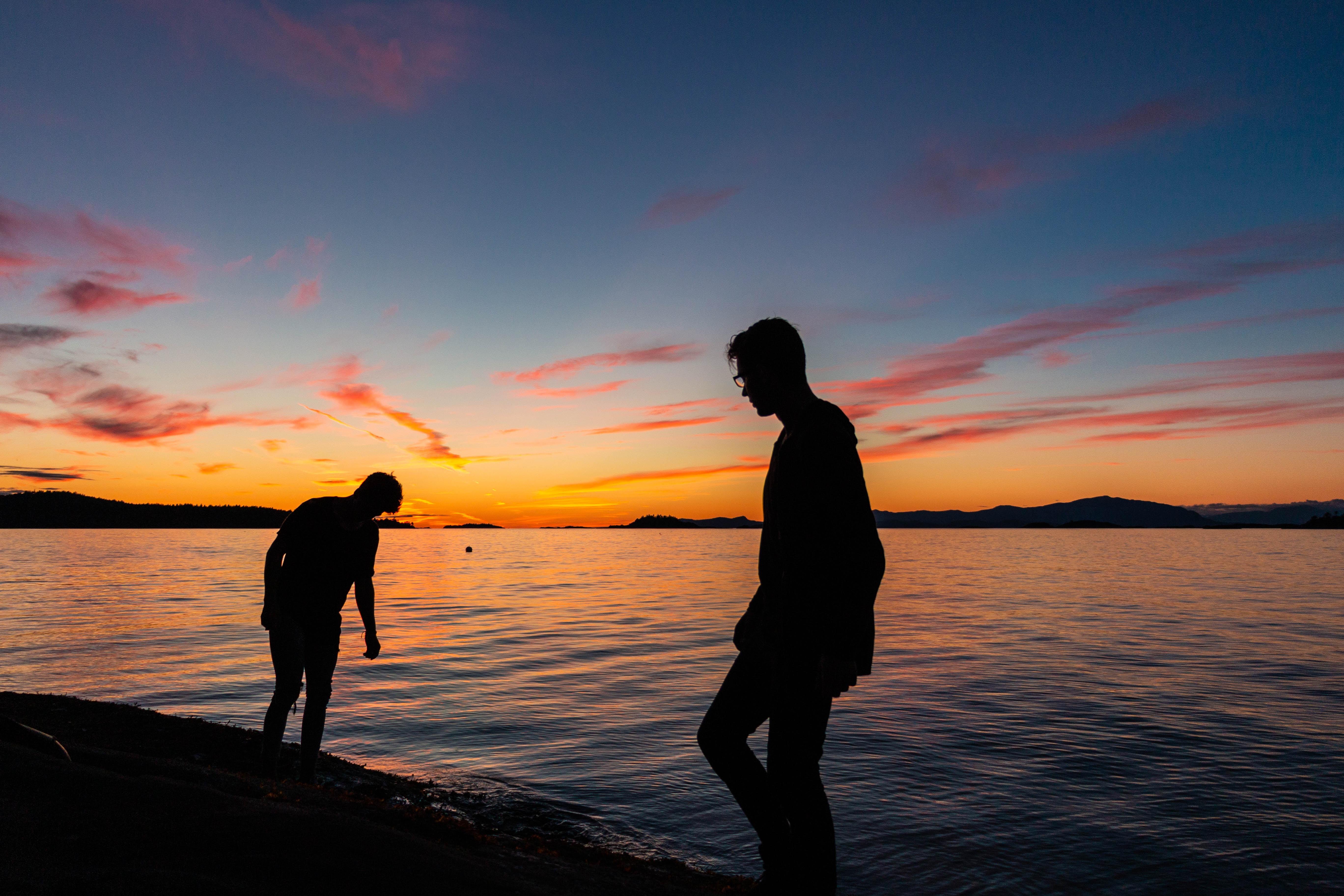 two men standing beside body of water