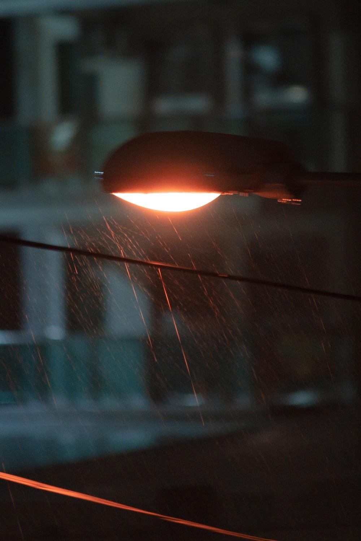 turned-on light post under the rain