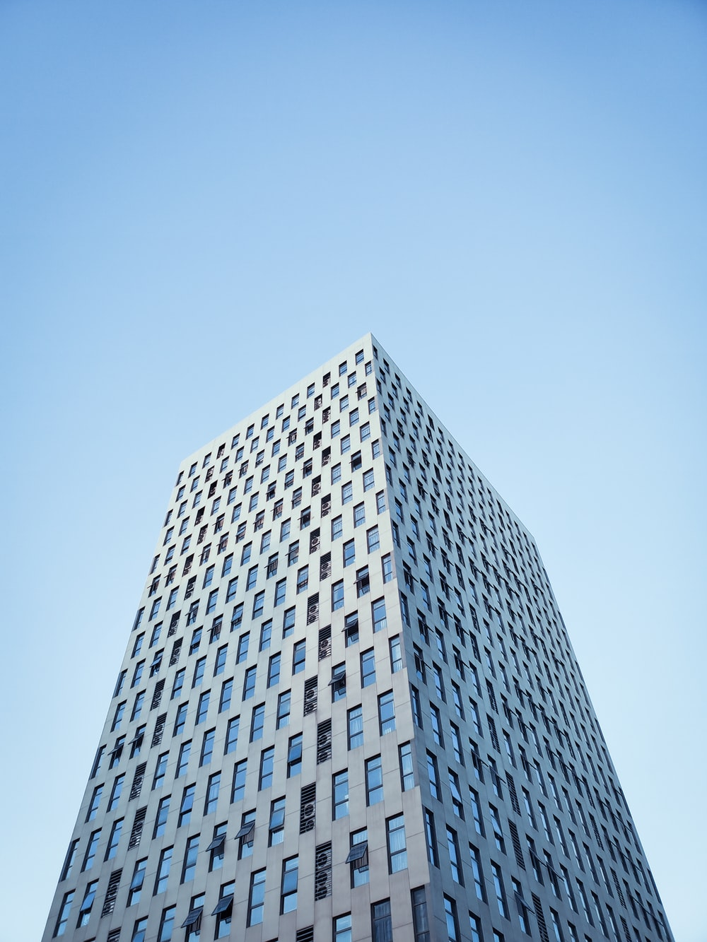 low angle photography of high rise building under clear blue sky