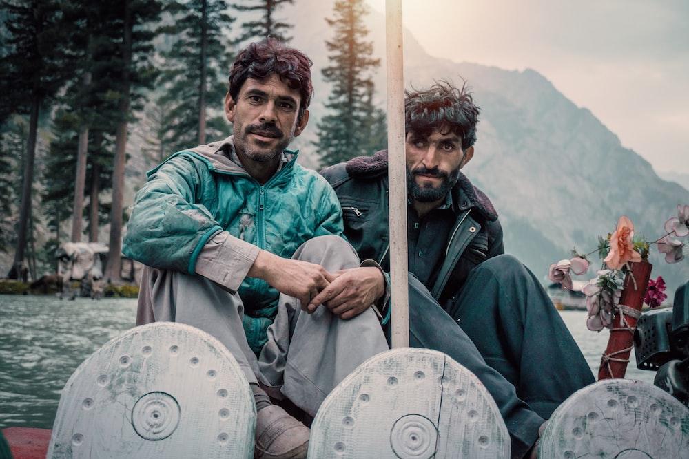 two men sitting on boat
